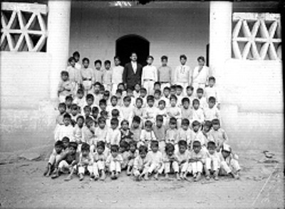 Niños indígenas con su profesor afuera de su escuela, retrato de grupo