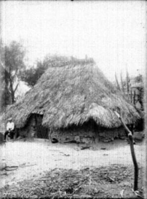 Hombre mestizo afuera de una vivienda indígena