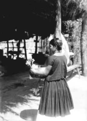 Mujer zapoteca con vasija decorada y planta en las manos
