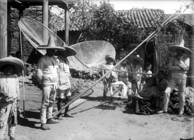 Indígenas purépechaS con redes para pesca en el patio de una casa