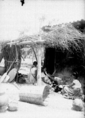 Mujeres otomíes sentadas afuera de su vivienda