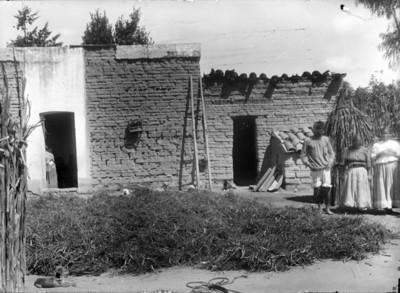 Mujeres y hombre mazahua frente a su vivienda