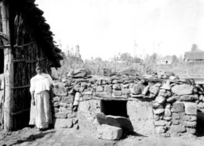 Mujer indígena afuera de su vivienda junto a un horno
