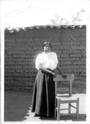 Mujer purépecha apoyada en una silla, retrato