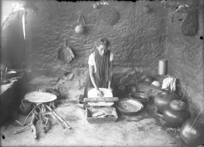 Mujer nahua muele alimentos en un metate