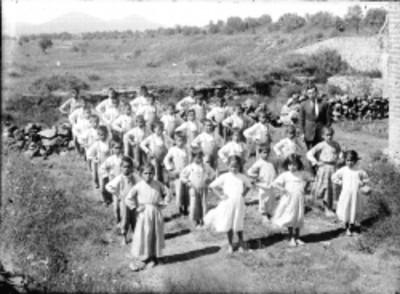 Niños formados realizan ejercicios en el patio de una escuela