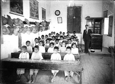 Alumnos indígenas y profesor en un salón de clases, retrato de grupo