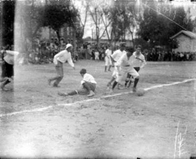Adolescentes juegan futbol en un campo deportivo
