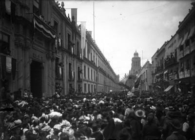 Multitud de personas rodean el carro alegórico de la pila bautismal del Hidalgo frente al Museo Nacional