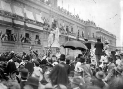 Gente rodea un carro alegórico frente a Palacio Nacional