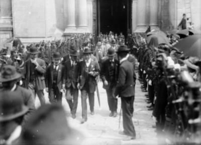 Hombres salen de un edificio durante evento de las Fiestas del Centenario