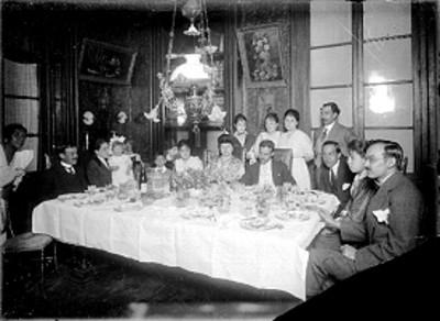 Alfonso Cravioto acompañado de hombres y mujeres en un banquete
