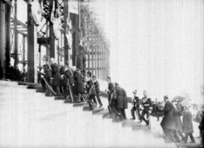Militares y funcionarios públicos suben escaleras para colocar la primera piedra de la construcción del Palacio Legislativo