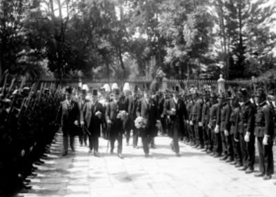 Hombres caminan con ofrenda a las tumbas de los Héroes de Independencia
