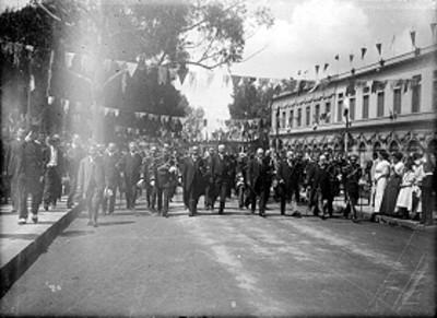Militares y funcionarios desfilan por una calle durante las fiestas del centenario