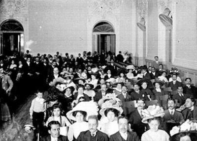 Gente en el interior de un salón durante ceremonia en las Fiestas del Centenario