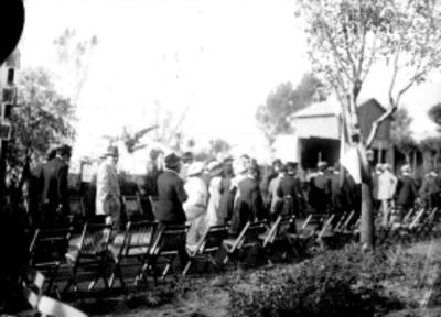 Asistentes a ceremonia se trasladan por jardín durante las fiestas del centenario