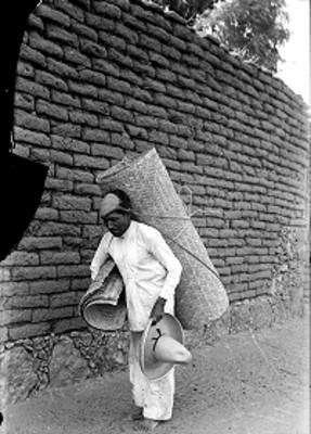 Vendedor de petates camina junto a muro de adobe