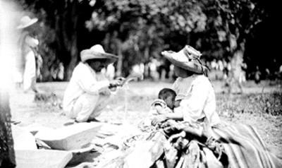 Mujer amamanta a su hijo junto a artesano tejiendo palma