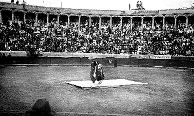 Charro y china poblana bailan en una plaza de toros