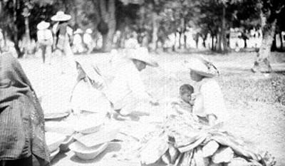 Mujeres y hombre venden artesanias en un parque