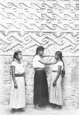 Mujeres junto a pared del edificio prehispánico en Mitla, reprografía