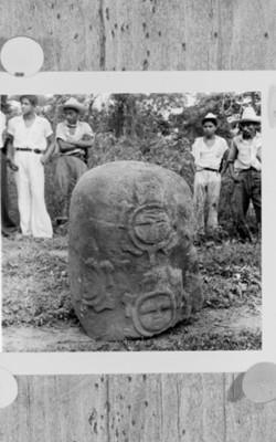 Hombres junto a una escultura de bajo relieve, reprografía