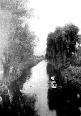 Hombres en canoa en el canal de Mexicalzingo