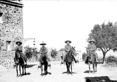 Charros a caballo afuera de una hacienda, retrato de grupo