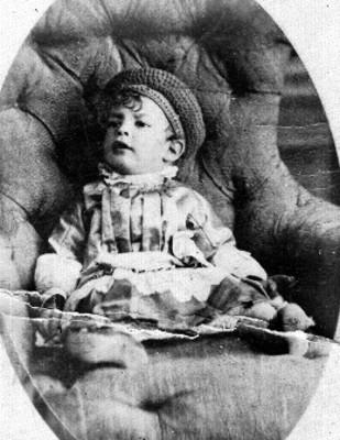 Niño con gorro sentado en un sillón, retrato
