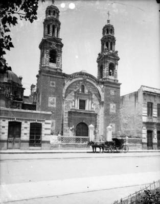 Carruaje frente a la fachada de una iglesia