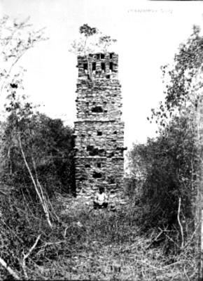 Hombre sentado frente a la torre, reprografía