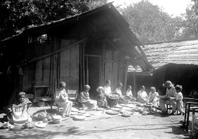 Indígenas limpian platos afuera de una choza