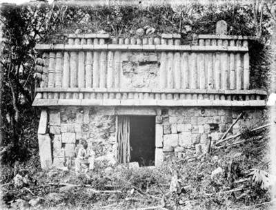 Hombre sentado frente a un edificio de Xpuhbiltuch, Yucatán, reprografía