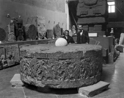 Hombres junto a la piedra de Tizoc exhibida en la Sala de Monolitos