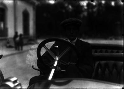 Agustín Caseaux abordo de un automóvil por una calle, retrato