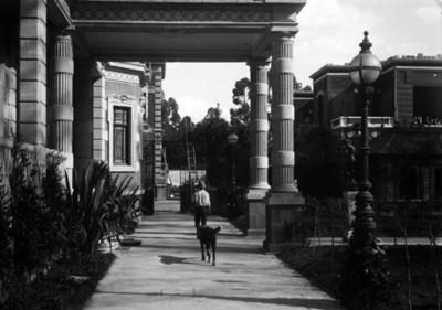 Sirviente con perro en el porche de la mansión Azurmendi