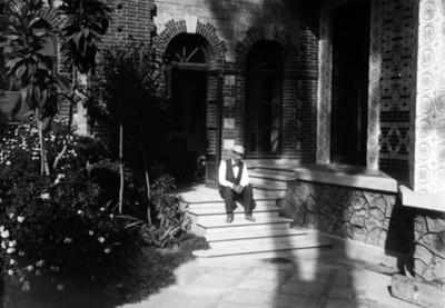 Hombre sentado en las escalinatas de la residencia Azurmendi, retrato