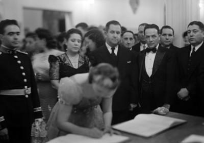 Mujer firma acta civíl en presencia de Manuel Ávila Camacho y esposa