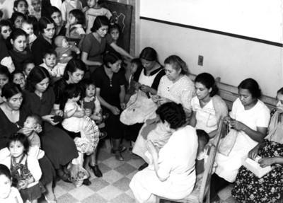 Mujeres con niños durante clase de tejido