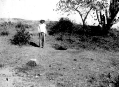 Hombre junto a tumba descubierta en las exploraciones, retrato