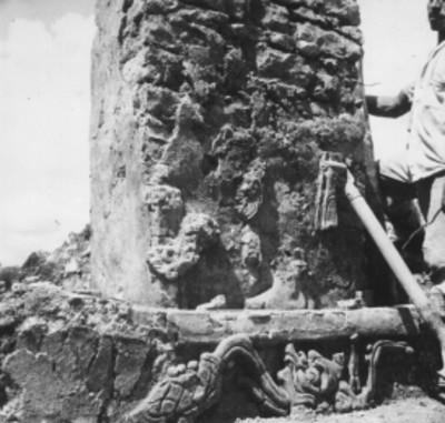 Hombre junto a tablero y pilastra de un templo, vista parcial