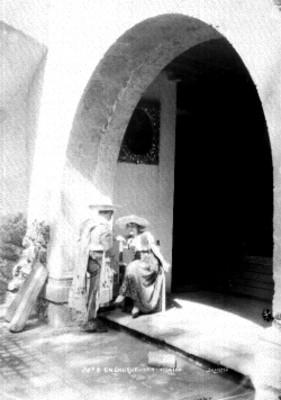 Hombre y mujer conversan al pie de una casa