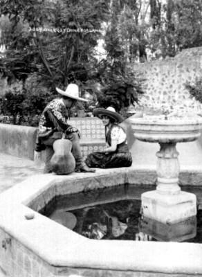 Pareja viste trajes folclóricos junto a una fuente