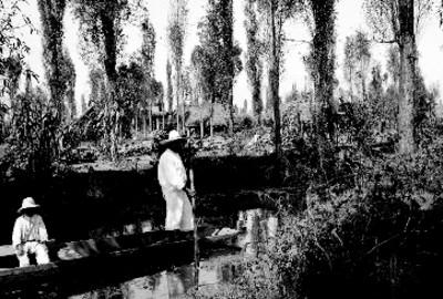 Hombre y niño indígenas sobre trajinera en el canal de Tláhuac
