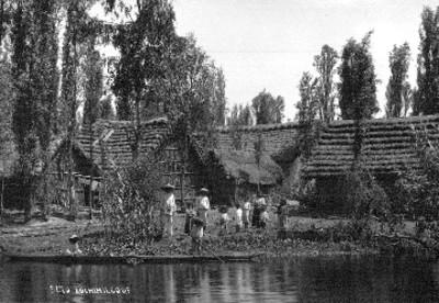 Familia indígena junto a chozas a orilla de un canal en Xochimilco, retrato de grupo