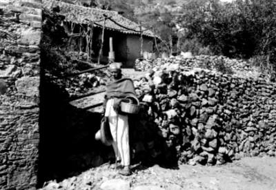 Anciano indígena junto a la entrada de una vivienda, retrato