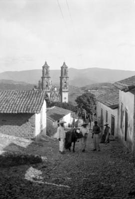 Hombres en una calle con iglesia de Santa Prisca al fondo