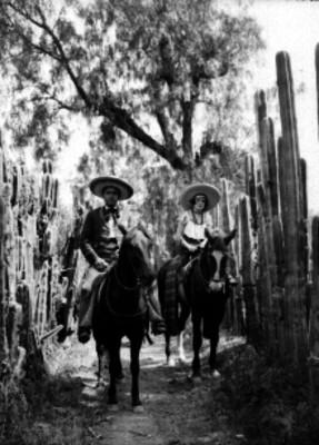 Hombre y mujer con trajes folclóricos montan caballos, retrato