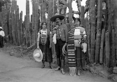 Charro y chinas poblanas junto a cactus, retrato